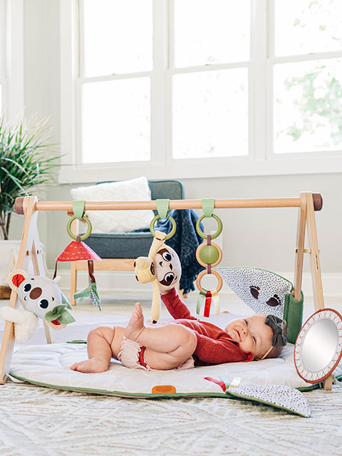 Boho style developmental baby gym with a wooden stand alone arch